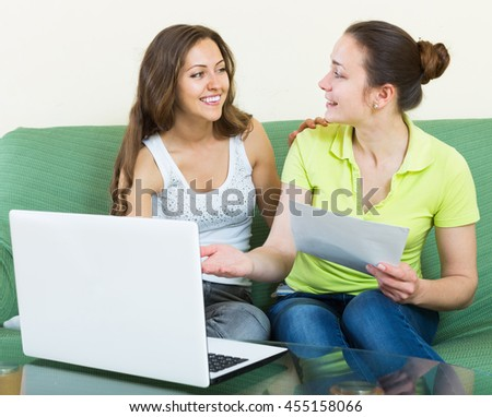 Smiling American women looking financial documents with laptop  in home interior