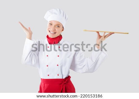 Smiling and cheerful female chef, cook or baker in uniform and hat isolated on white background. - stock photo