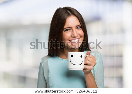 Smiling and cheerful woman holding a smiling cup - stock photo