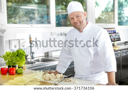 Smiling and confident chef standing in large kitchen - stock photo