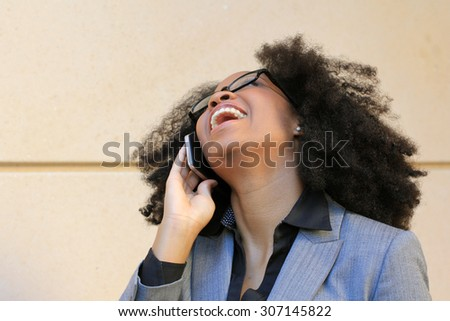 Smiling and Happy Professional African American Business Woman College Student With Black Hair Laughing and Talking on the Phone