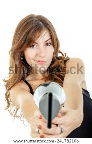 Smiling and happy professional caucasian brunette female hairdresser holding hairdryer like gun and pointing at camera wiith curious face expression, isolated on white backgropund - stock photo