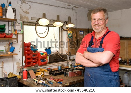 Smiling and happy senior craftsman in his garage - stock photo