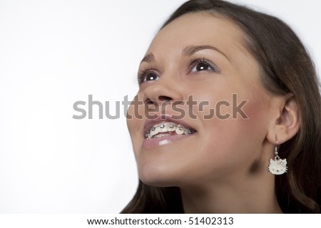 smiling and happy young girl with dark hair with bracket system isolated over white - stock photo