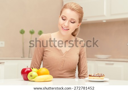Smiling and healthy. Young happy and glad woman sitting at the table looking on the plate with fruit prefers apples, oranges and banana to donut