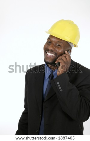 Smiling architect, engineer, or supervisor in yellow hardhat talking on a cellphone. - stock photo