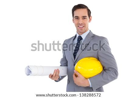 Smiling architect holding plans and hard hat on white background - stock photo