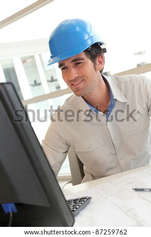 Smiling architect in office working on desktop computer
