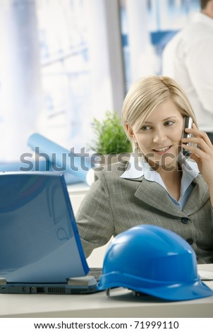 Smiling architect talking on phone looking at computer screen in office.? - stock photo