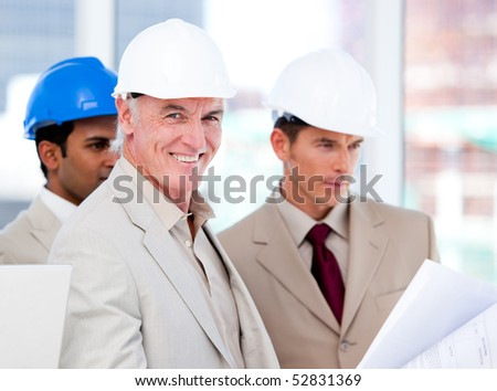 Smiling architect team working on a building project in a company - stock photo