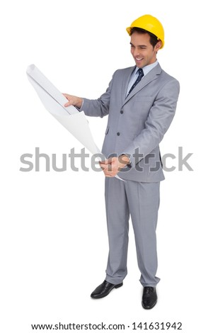Smiling architect with hard hat looking at plans on white background - stock photo