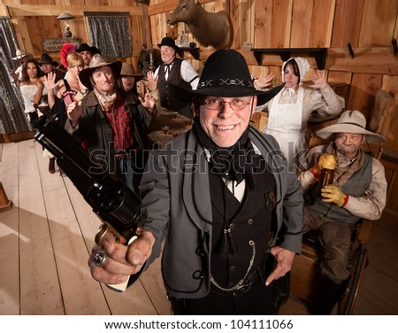 Smiling armed sheriff and group of people with hands up in saloon - stock photo