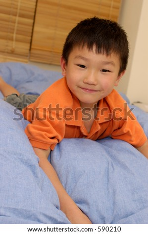 smiling asian boy on bed - stock photo