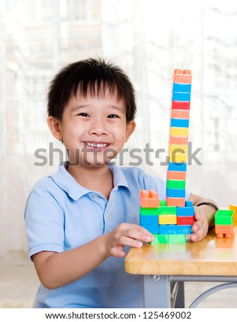 smiling asian boy playing with building blocks - stock photo