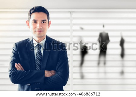 Smiling Asian businessman crossing his arms - leader and success businessman concept - stock photo