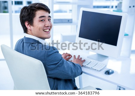 Smiling asian businessman using his computer in his office - stock photo