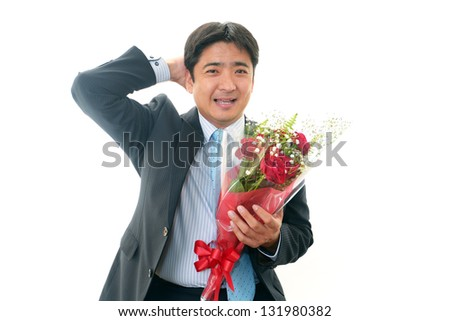 Smiling Asian businessman with a bouquet