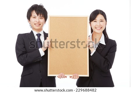 smiling Asian businesswoman and businessman with Bulletin Board - stock photo