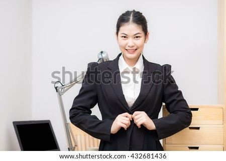 Smiling asian businesswoman with laptop computer posting in white office looking at the camera