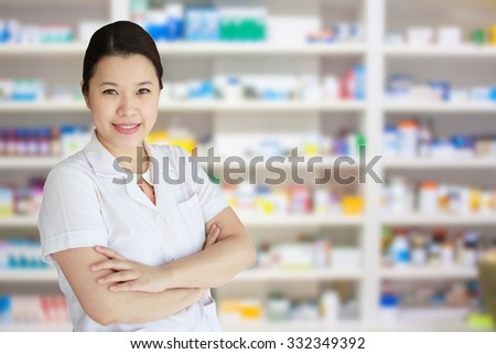 smiling asian female pharmacist with pharmacy drugstore shelves background - stock photo