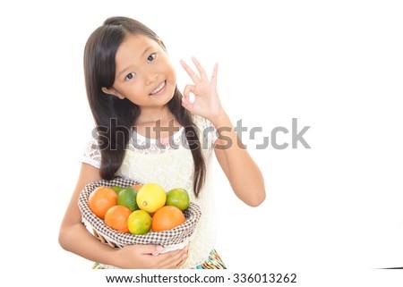 Smiling Asian girl holding fruits - stock photo