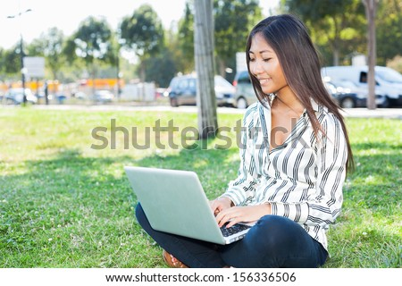 Smiling asian girl using a laptop sitting on the grass