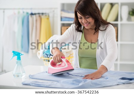 Smiling Asian housewife ironing freshly washed clothes in utility room