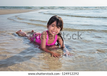 Smiling asian little girl playing on beach - stock photo
