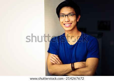 Smiling asian man standing with arms folded at home - stock photo