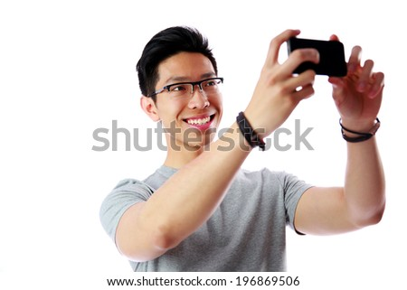 Smiling asian man taking photo with smartphone over white background