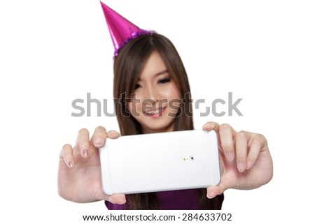 Smiling Asian party girl taking picture with her smartphone camera, isolated on white background, selective focus on phone - stock photo