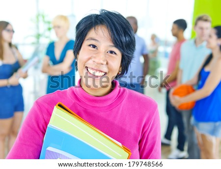 Smiling Asian Student with Books in School - stock photo