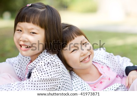 smiling asian twin girls sitting - stock photo