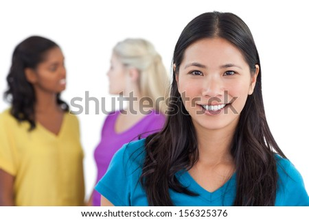 Smiling asian woman looking at camera with two women behind her on white background - stock photo