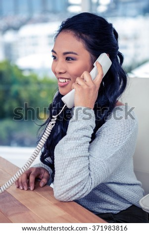 Smiling Asian woman on phone call in office