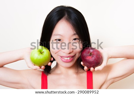 Smiling asian woman showing a green and a red apple in hands on white background