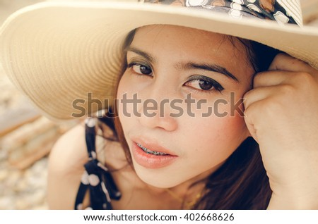 Smiling Asian woman wearing dental braces grinning to show her teeth, closeup headshot - stock photo