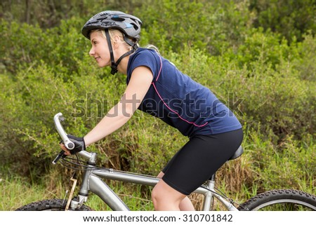 Smiling athletic blonde mountain biking in the nature