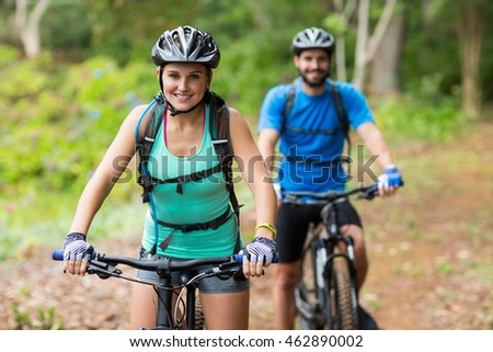 Smiling athletic couple cycling in forest