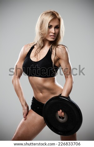 Smiling athletic woman pumping up muscles with barbell on gray background - stock photo