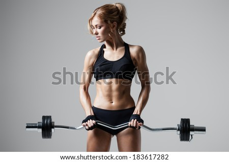 Smiling athletic woman pumping up muscules with barbell on gray background - stock photo