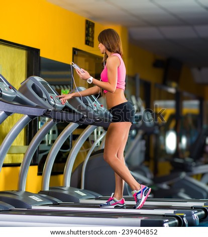 Smiling athletic woman training on a running machine with earphones in a fitness center - stock photo