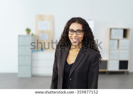 Smiling attractive African American businesswoman standing in a large open office looking at the camera with a beaming smile, upper body and copy space - stock photo
