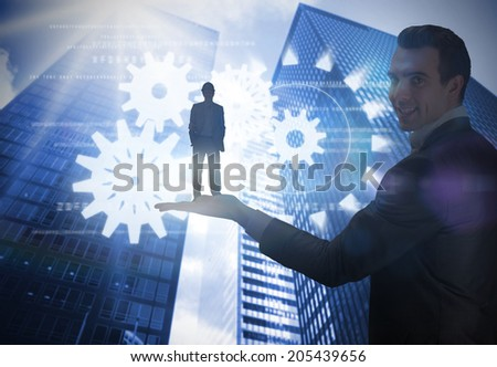 Smiling attractive architect on phone held by giant businessman holding plans against low angle view of skyscrapers - stock photo