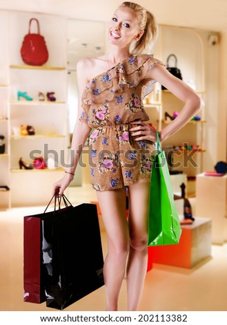 Smiling attractive beautiful blonde woman shopping. Girl holding bags, looking at ca,era. - stock photo