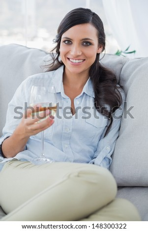 Smiling attractive brunette drinking white wine in her living room