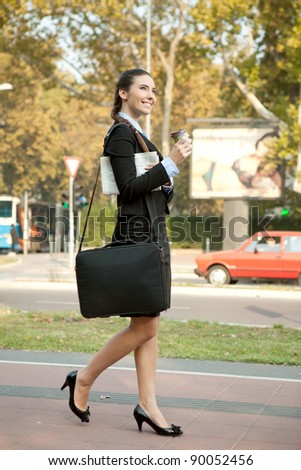 smiling, attractive businesswoman holding coffee and  walking on street - stock photo
