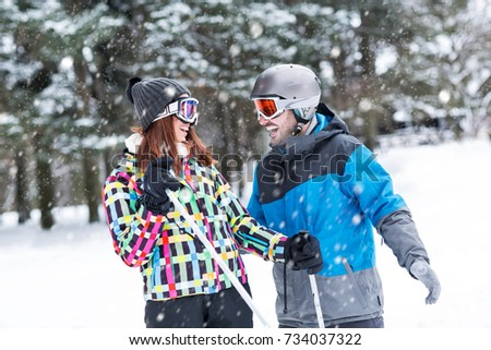 Smiling attractive couple enjoy at top of the high mountain while snow falling