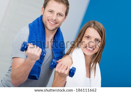 Smiling attractive couple working out in a gym flexing their arms while holding dumbbells to strengthen their muscles as they stand together smiling at the camera - stock photo