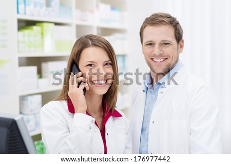 Smiling attractive female pharmacist chatting on the phone watched by a handsome male colleague as they stand in the pharmacy - stock photo